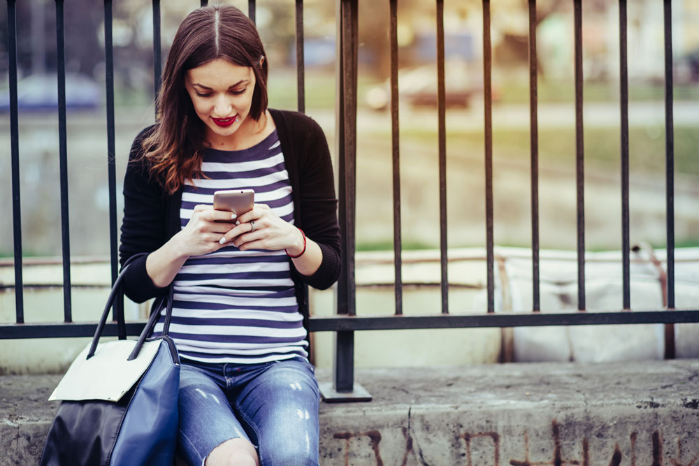 Woman views a Facebook advertisement on her mobile phone
